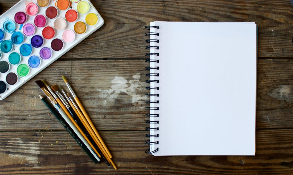 A desk with watercolors, paintbrushes, pencils, and a notebook perfect for creative nonfiction.