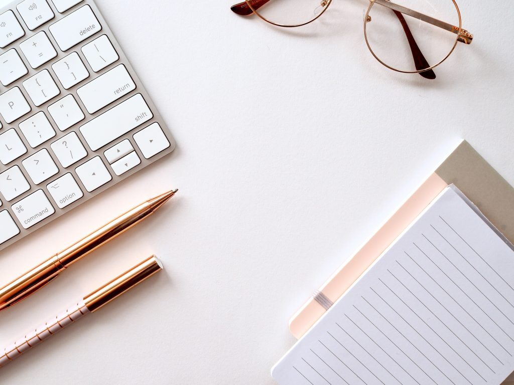 A desktop with a keyboard, glasses, writing utensils, and a notebook - everything needed to write guest posts.