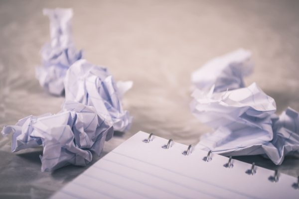 A blank notebook sits in the foreground, with crumpled pieces of paper balled up in the background from a reluctant writer with a serious case of writer's block.