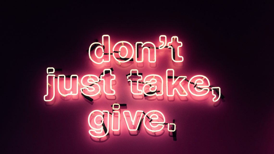 """A red, pink, and white sign lights up to read, """"don't just take, give."""""""