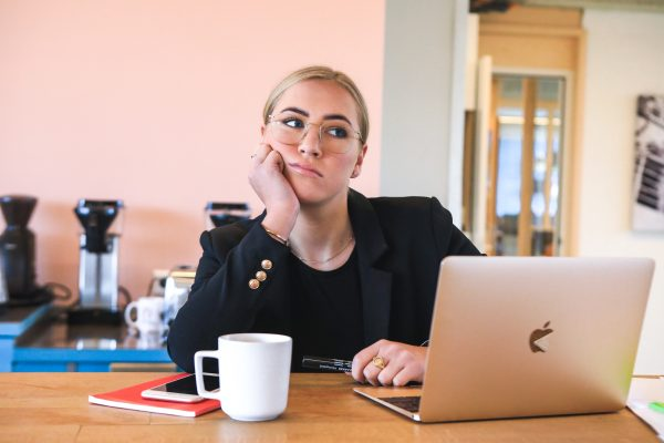 """A woman sits at her desk with a laptop and a cup of coffee, hand on her chin. She's staring off in the distance, thinking """"how do I stop procrastinating?"""""""
