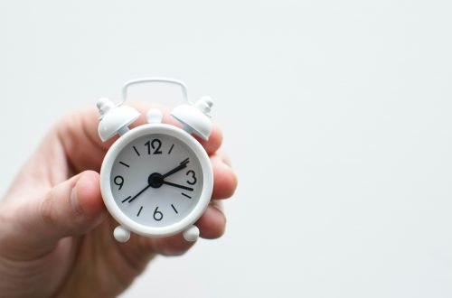 A small white clock slips through a person's fingers.